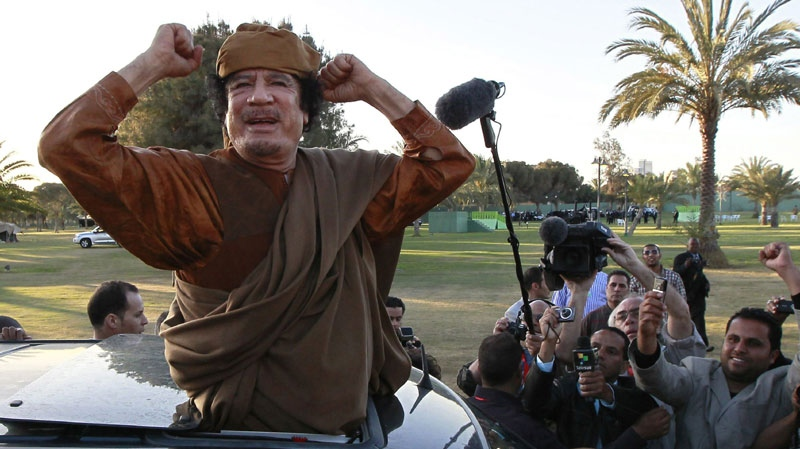 In this April 10, 2011 file photo, Libyan leader Moammar Gadhafi gestures to his supporters in Tripoli, Libya. (AP Photo/Pier Paolo Cito, File)