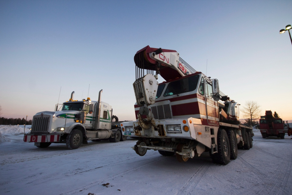 A fleet of rail service trucks arrives at the Tobique-Plex in Plaster Rock, N.B. early on Wednesday Jan. 8, 2014. (Tom Bateman / THE CANADIAN PRESS)