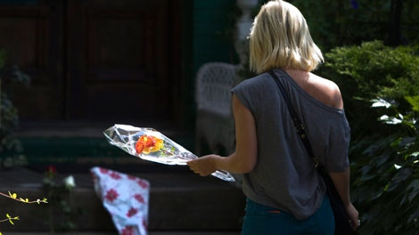 Brittany Bolton walks toward the front door of Jack Layton's Toronto home to lay flowers in condolence of Layton's passing, Monday, Aug. 22, 2011. (Darren Calabrese / THE CANADIAN PRESS)