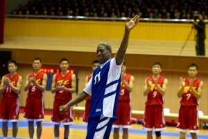 Dennis Rodman waves to North Korean leader Kim Jong Un, seated above in the stands, after singing Happy Birthday to Kim before an exhibition basketball game with U.S. and North Korean players at an indoor stadium in Pyongyang, North Korea on Wednesday, Jan. 8, 2014. (AP / Kim Kwang Hyon)