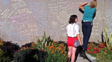 Citizens write notes on a condolence wall at Nathan Phillips Square in Toronto on Monday, Aug. 22, 2011. (PJMixer / Flickr)