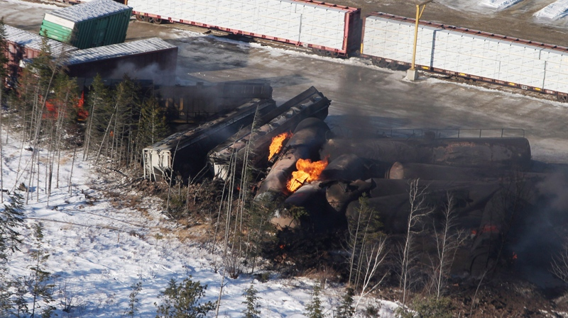 Derailed train cars burn in Plaster Rock, N.B., on Wednesday, Jan.8, 2014. The federal Transportation Safety Board says it will conduct a full investigation into the derailment that saw 19 cars in a 122-car freight train jump the tracks (CP / Tom Bateman)