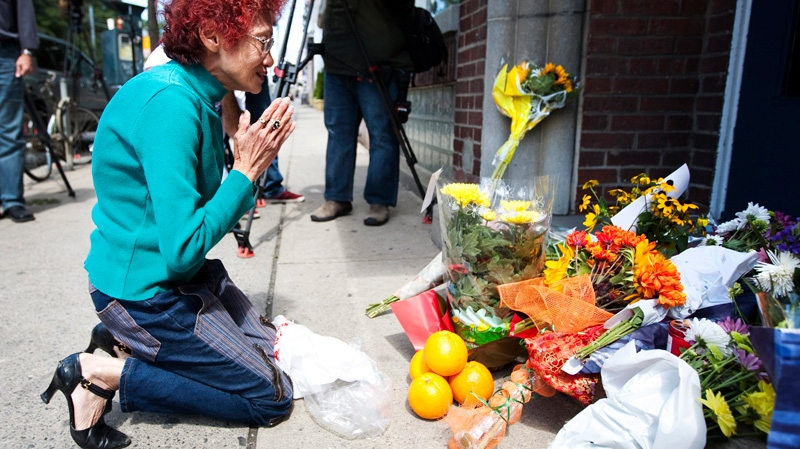 Linda Truong prays in front of a vigil on the steps of Jack Layton's constituency office in Toronto Monday, Aug. 22, 2011. (Darren Calabrese / THE CANADIAN PRESS)