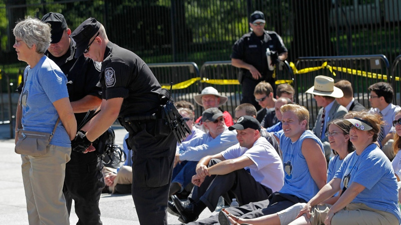An environmental activist is handcuffed outside the White House in Washington, Monday, Aug. 22, 2011, as they continue a civil disobedience campaign against a proposed oil pipeline from Canada to the U.S. Gulf Coast. (AP / J. Scott Applewhite)