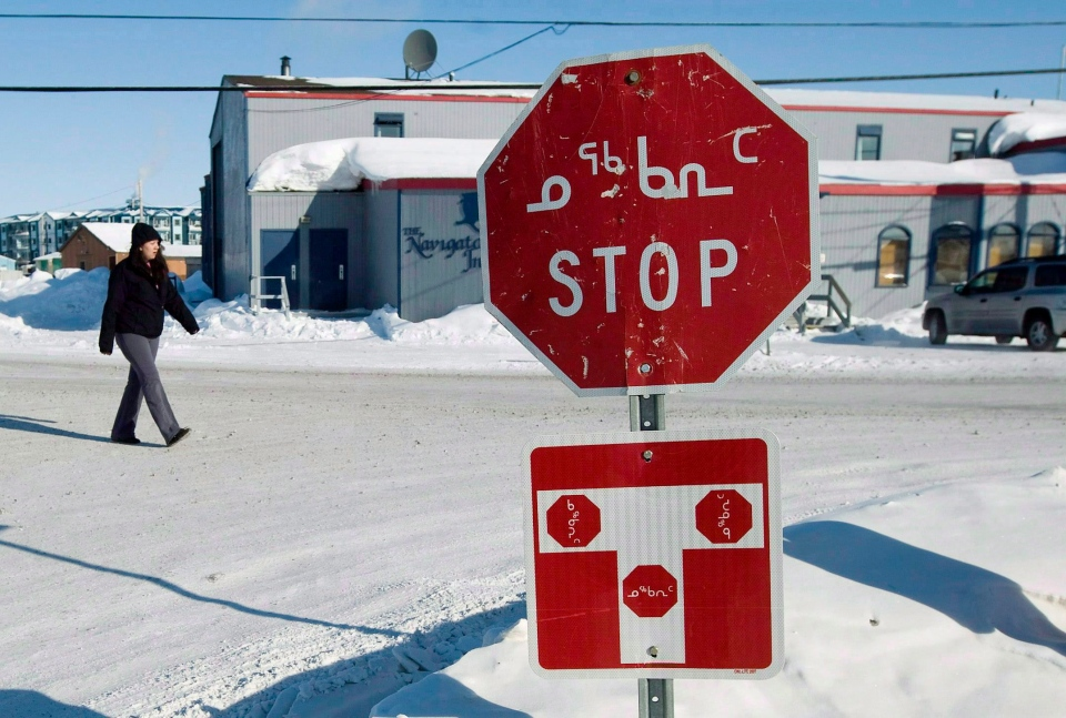 A person walks past a stop sign displayed in both English and Inuktitut in the city of Iqaluit, Nunavut on March 28, 2009.(Nathan Denette / THE CANADIAN PRESS)