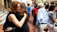 Co-workers Susan Sproul, left, and Susan Davidson hug after evacuating from their building after an earthquake was felt in Baltimore, Tuesday, Aug. 23, 2011.  (AP / Patrick Semansky)