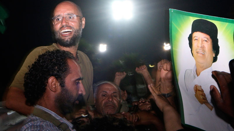 Moammar Gadhafi's son, Seif al-Islam, top left, gestures to troops loyal to his father in Tripoli, Libya, Tuesday, Aug. 23, 2011. (AP / Imed Lamloum)