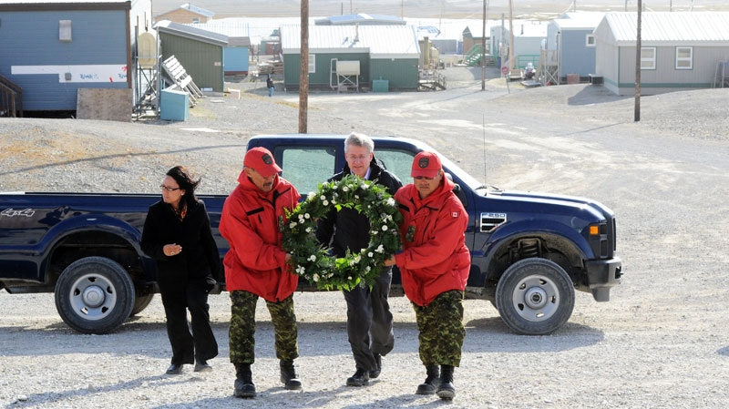 Prime Minister Stephen Harper, walks behind two Arctic Rangers as they carry a wreath in memory of those who lost their lives on First Air flight 6560 which crashed in Resolute Saturday, killing 12 and injuring three, during his Northern trip on Tuesday, August 23, 2011. Sean Kilpatrick / THE CANADIAN PRESS