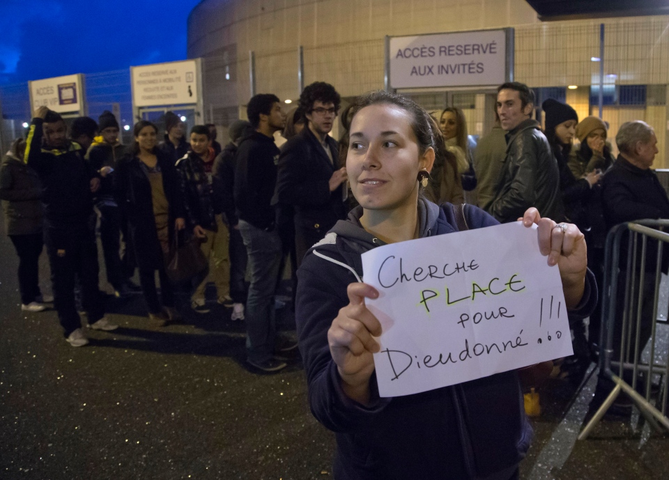 A woman holds a paper which reads 'looking for a ticket for Dieudonne' outside the Zenith arena where French comic Dieudonne M'Bala M'Bala will have his show in Nantes, France, Thursday, Jan. 9, 2014. (AP / Michel Euler)