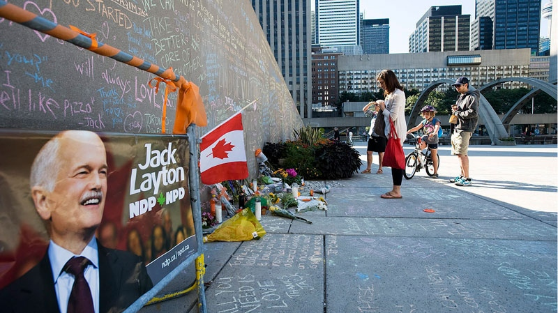 People read from a wall which has been made into a tribute to the late NDP leader Jack Layton at Nathan Phillips Square in Toronto on Tuesday, Aug. 23, 2011. (Aaron Vincent Elkaim / THE CANADIAN PRESS)