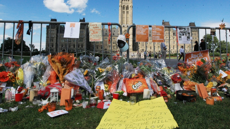 A case of Orange Crush along with flowers and other mementos are left on Parliament Hill to pay tribute to NDP leader Jack Layton, Tuesday Aug. 23, 2011, in Ottawa where a makeshift memorial has formed after Layton died early Monday. (Fred Chartrand / THE CANADIAN PRESS)