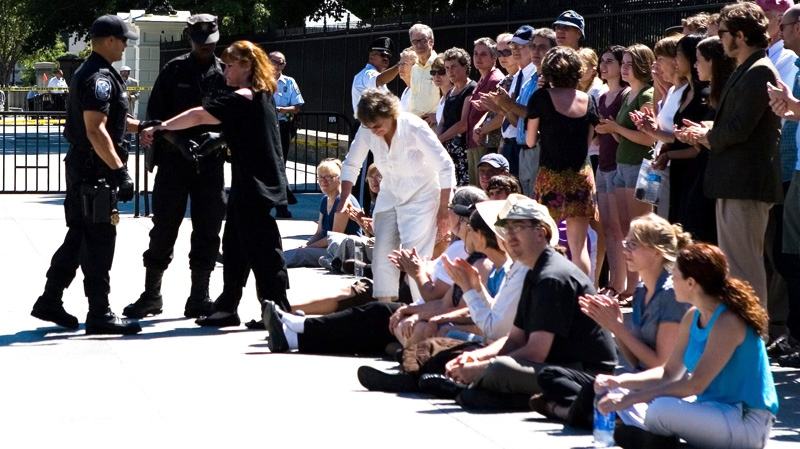 Canadian actress Margot Kidder, left, is handcuffed by police as other environmentalists applaud outside the White House in Washington, Tuesday, Aug. 23, 2011. (Keith Lane / THE CANADIAN PRESS)