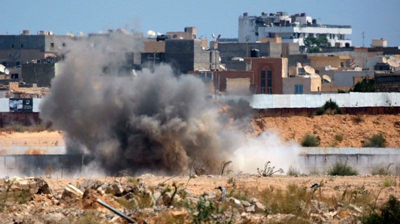 An explosion is seen near Gadhafi's main compound in the Bab al-Aziziya district in Tripoli, Libya, Tuesday, Aug. 23, 2011. (AP / Sergey Ponomarev)
