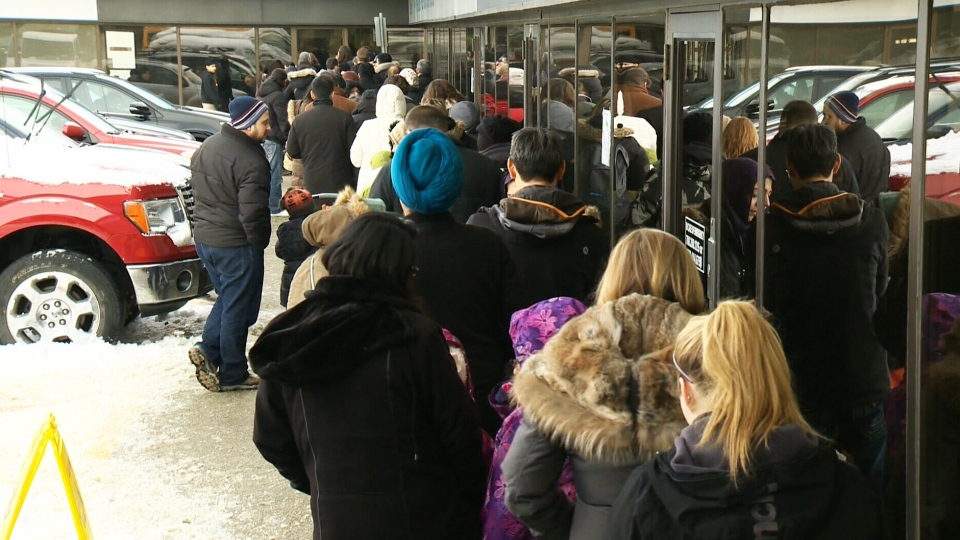 Residents in Alberta wait in line for hours for flu vaccines that are starting to run low on Jan. 9, 2014.