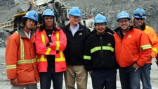 Prime Minister Stephen Harper, middle, poses for a group photo with a group of miners as he tours the Meadowbank Mine facility in Meadowbank Mine, Nunavut on Wednesday, August 24, 2011.  Sean Kilpatrick / THE CANADIAN PRESS
