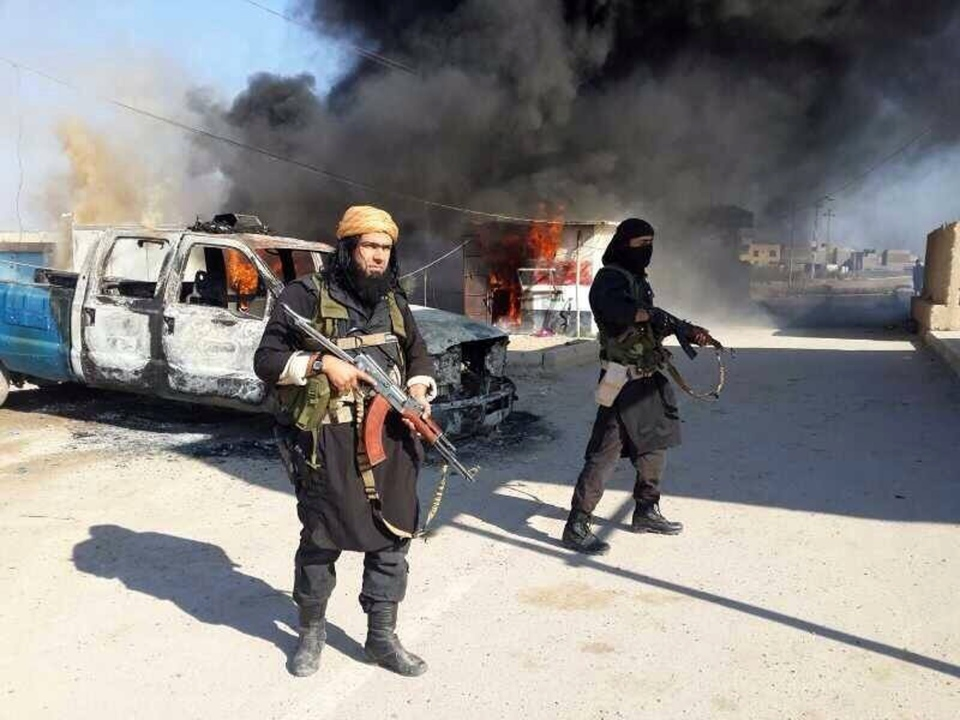 This undated image posted on a militant website on Jan. 4, 2014, which is consistent with other AP reporting, shows Shakir Waheib, a senior member of the al-Qaida-linked Islamic State of Iraq and the Levant (ISIL), left, next to a burning police vehicle in Iraq's Anbar Province. (AP Photo via militant website)