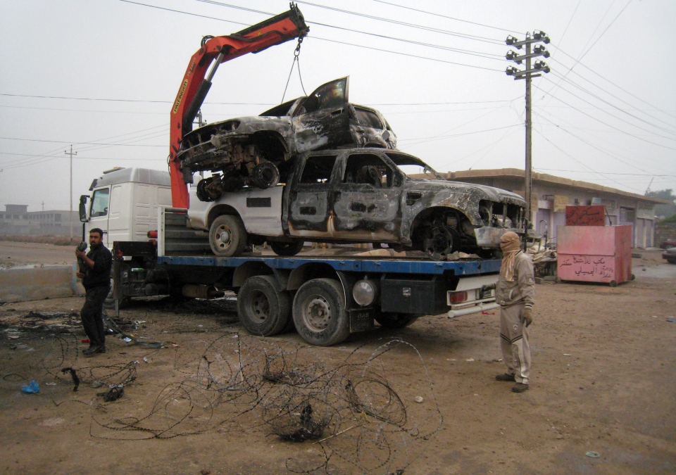 Gunmen remove police vehicles destroyed during clashes in Fallujah, 65 kilometres west of Baghdad, Iraq, Friday, Jan. 10, 2014. (AP Photo)
