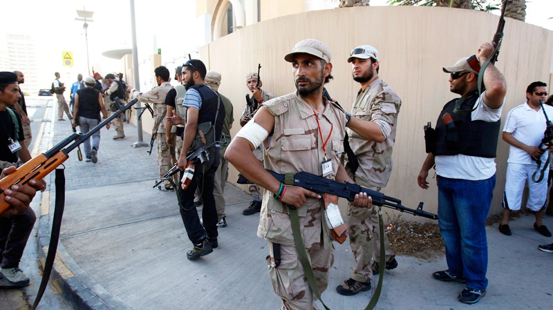 Libyan rebels patrol to try and find Moammar Gadhafi's relatives as they got rumors that one of his son was hiding inside the building, in Tripoli, Libya, Wednesday, Aug. 24, 2011. (AP / Francois Mori)