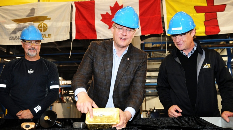 Prime Minister Stephen Harper holds a $1.8-million bar of gold as he tours Agnico-Eagle's Meadowbank mine facility in Meadowbank Mine, Nunavut on Wednesday, Aug. 24, 2011. (Sean Kilpatrick /  THE CANADIAN PRESS)