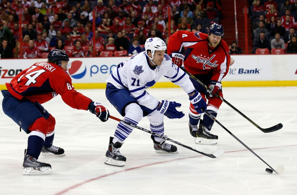 Toronto Maple Leafs right wing David Clarkson (71) skates with the puck between Washington Capitals center Mikhail Grabovski (84), from Germany, and defenseman John Erskine (4) during the second period of an NHL hockey game in Washington on  Friday, Jan. 10, 2014. (AP / Alex Brandon)