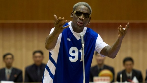 Dennis Rodman sings Happy Birthday to North Korean leader Kim Jong Un, seated above in the stands, before an exhibition basketball game at an indoor stadium in Pyongyang, North Korea on Wednesday, Jan. 8, 2014. (AP /  Kim Kwang Hyon