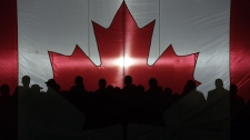 Soldiers and rescue personnel are silhouetted against a Canada flag prior to a speech by Prime Minister Stephen Harper as he partakes in Operation Nanook 2011 in Resolute, Nunavut on Tuesday, Aug. 23, 2011. (Sean Kilpatrick / THE CANADIAN PRESS)