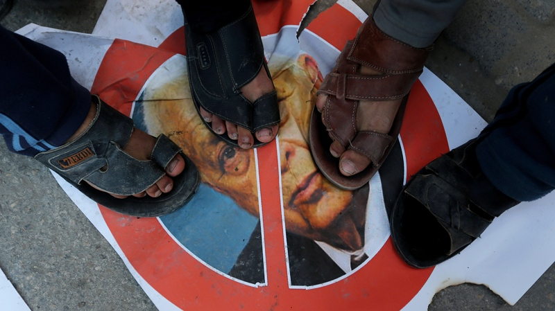Palestinians stand over a picture of the former Israeli Prime Minister Ariel Sharon in Khan Younis, southern Gaza Strip, Saturday, Jan. 11, 2014. (AP Photo/Hatem Moussa)