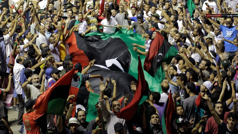 Libyans celebrate overrunning Moammar Gadhafi's main compound Bab al-Aziziya in Tripoli, Libya, early Wednesday, Aug. 24, 2011. (AP / Sergey Ponomarev)