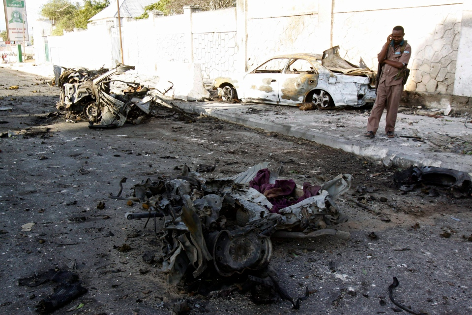 A Somali soldier stands near the wreckage of cars after bombs went off at the gate of a hotel in Mogadishu, Somalia, Thursday, Jan. 2, 2014. (AP / Farah Abdi Warsameh)