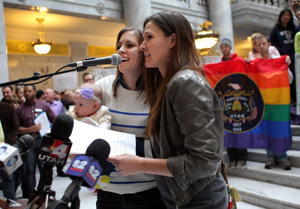 Megan, left, and Candace Berrett, right, hold their daughter Quinn as they speak to supporters of gay marriage during a rally at the Utah State Capitol in Salt Lake City on Friday, Jan. 10, 2014. (AP / Steve C. Wilson)