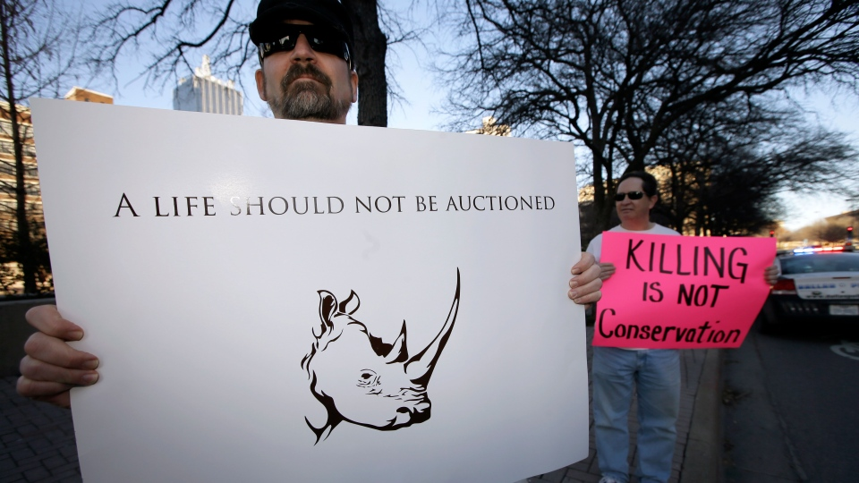 Bob Fretwell of Mesquite, Texas, holds a sign protesting outside the Dallas Convention Center where the Dallas Safari Club is holding it's weekend show and auction in Dallas on Saturday, Jan. 11, 2014. (AP / Tony Gutierrez)