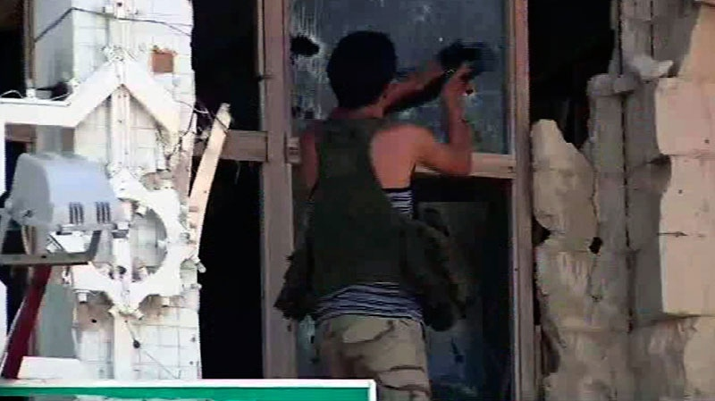 A rebel fighter smashes a window with his rifle in Moammar Gadhafi's Bab al-Aziziya fortress-like compound in Tripoli, Wednesday, Aug. 24, 2011.