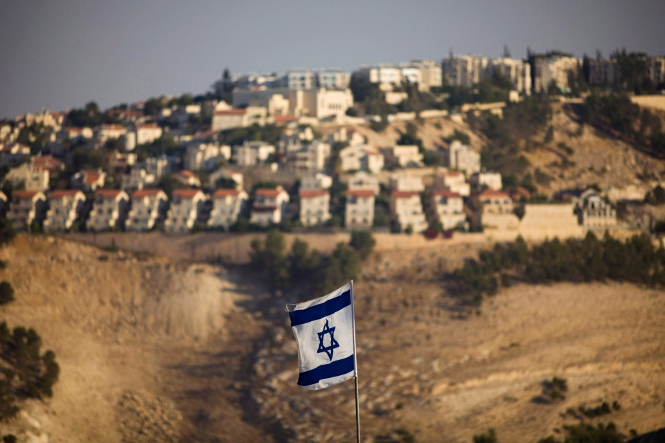 An Israeli flag is seen in front of the West Bank Jewish settlement of Maaleh Adumim, on the outskirts of Jerusalem, in this 2009 file photo (AP Photo/Bernat Armangue