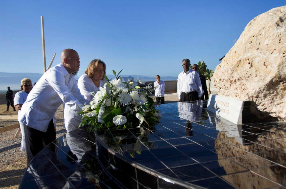 Haiti's President Michel Martelly, left, and first lady Sophia Martelly, center, place a bouquet of flowers at a monument in memory of the victims of the 2010 earthquake, during a memorial service at Titanyen, a mass burial site for earthquake victims, north of Port-au-Prince, Haiti, Sunday, Jan. 12, 2014.  (AP Photo/Jean Marc Herve Abelard)