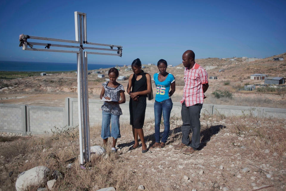 Relatives pray next to a cross in remembrance of family members who died in the 2010 earthquake during a memorial service in Titanyen, north of Port-au-Prince, Haiti, Sunday, Jan. 12, 2014. (AP Photo/Jean Marc Herve Abelard)