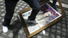 Libyan expatriates and embassy personnel stomp on the portrait of an embattled Libyan strongman Col. Moammar Gadhafi Wednesday Aug. 24, 2011 at the Libyan Embassy at suburban Makati city east of Manila, Philippines. (AP Photo/Bullit Marquez)