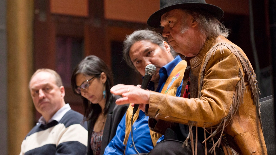 Singer Neil Young, right, speaks in front of climate scientist Andrew Weaver, left, Indigenous rights advocate Eriel Derenger, second left, and Athabasca Chipewyan Chief Allan Adam during a press conference for the 'Honour the Treaties' tour, a series benefit concerts being held to raise money for legal fight against the expansion of the Athabasca oilsands in northern Alberta and other similar projects, in Toronto, Sunday January 12, 2014. (Mark Blinch / THE CANADIAN PRESS)