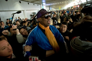 Former NBA basketball player Dennis Rodman is followed by journalists as he arrives at the Capital International Airport in Beijing from Pyongyang, Monday, Jan. 13, 2014.  (AP / Alexander F. Yuan)