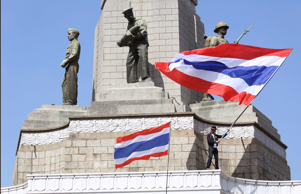 An anti-government protester waves a national flag during a rally at the Victory Monument in Bangkok, Thailand, Monday, Jan. 13, 2014. (AP / Apichart Weerawong)