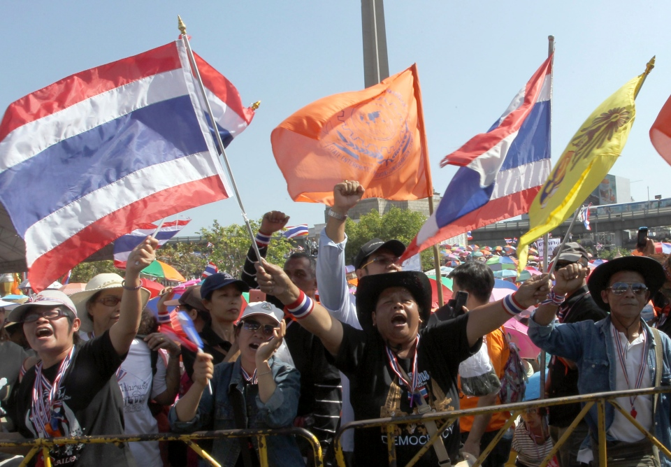 Anti-government protesters wave flags and chant slogans during a rally at the Victory Monument in Bangkok, Thailand Monday, Jan. 13, 2014. (AP / Apichart Weerawong)