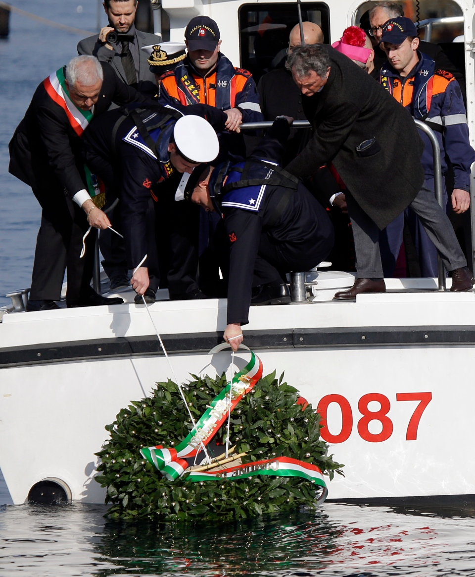 A wreath is being lowered into the water by Italian Navy personnel near the Costa Concordia near the shipwrecked Costa Concordia off the coast of the Tuscan Island of Giglio, Italy, Monday, Jan. 13, 2014. (AP / Gregorio Borgia)