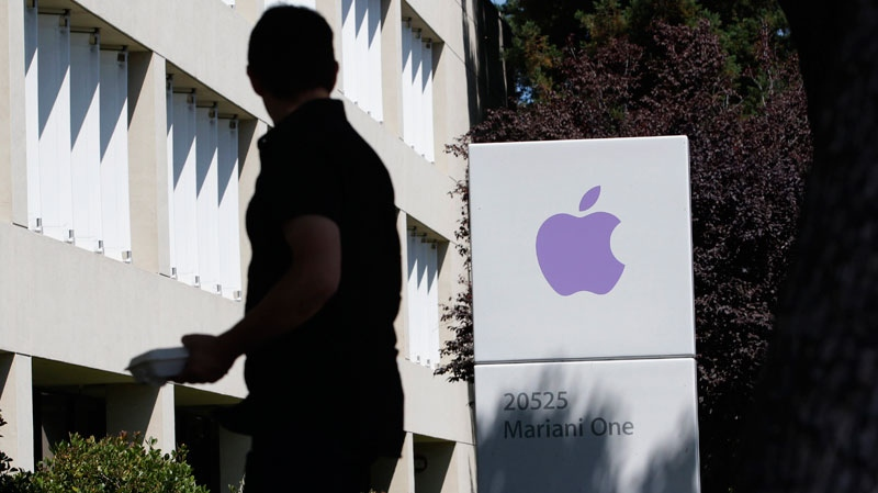 An Apple employee walks between Apple buildings at Apple headquarters in Cupertino, Calif., Thursday, Aug. 25, 2011. (AP / Paul Sakuma)