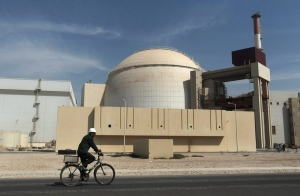In this Oct. 26, 2010 file photo, a worker rides a bicycle in front of the reactor building of the Bushehr nuclear power plant, just outside the southern city of Bushehr. (Mehr News Agency / Majid Asgaripour)