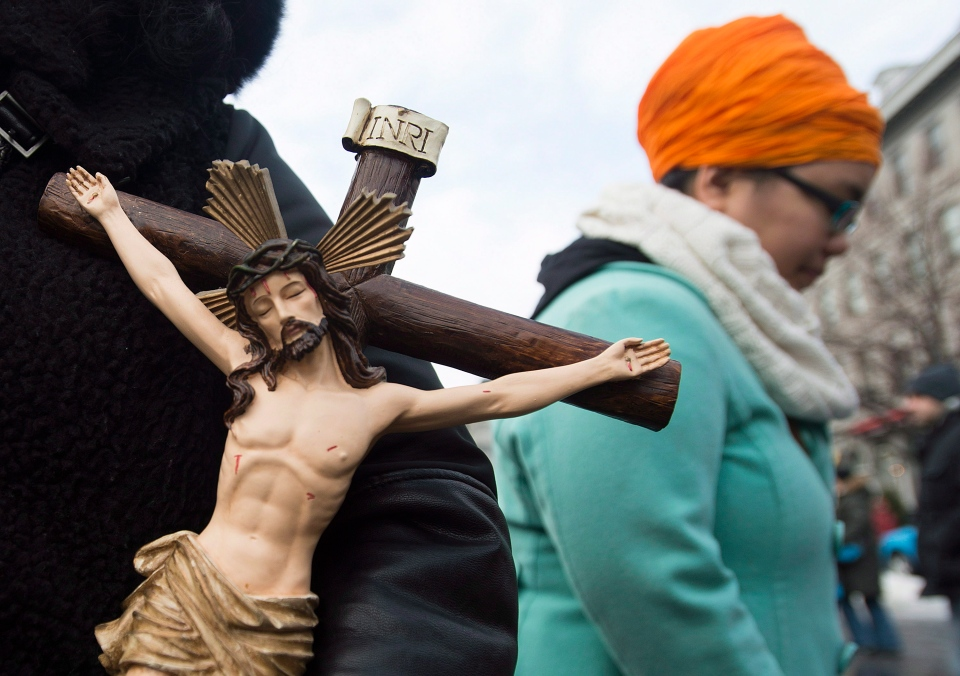 A woman holds a crucifix to oppose the proposed Quebec Values Charter during a gathering in Montreal, Sunday, Jan. 12, 2014. (Graham Hughes / THE CANADIAN PRESS)