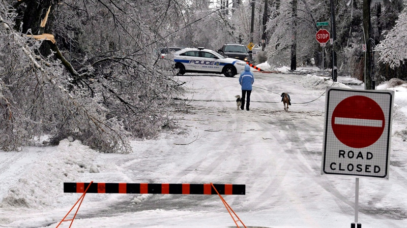 A pedestrian walks down a street still closed due to downed power lines and trees in Brampton, Ont., Monday, December 23, 2013. (THE CANADIAN PRESS / J.P. Moczulski)