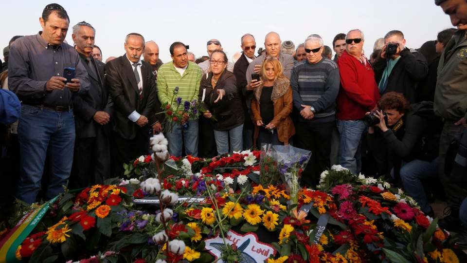 Israelis stand around the grave of former Israeli Prime Minister Ariel Sharon after his funeral during his funeral near Sycamore Farm, Sharon's residence in southern Israel, Monday, Jan. 13, 2014. (AP /Baz Ratner)