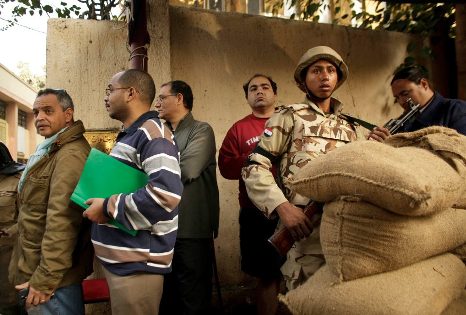 An Egyptian army soldier stands guard as voters line up outside a polling station for the first day in the country's constitutional referendum in the upscale neighborhood of Zamalek in Cairo, Egypt, Tuesday, Jan. 14, 2014. (AP / Maya Alleruzzo)