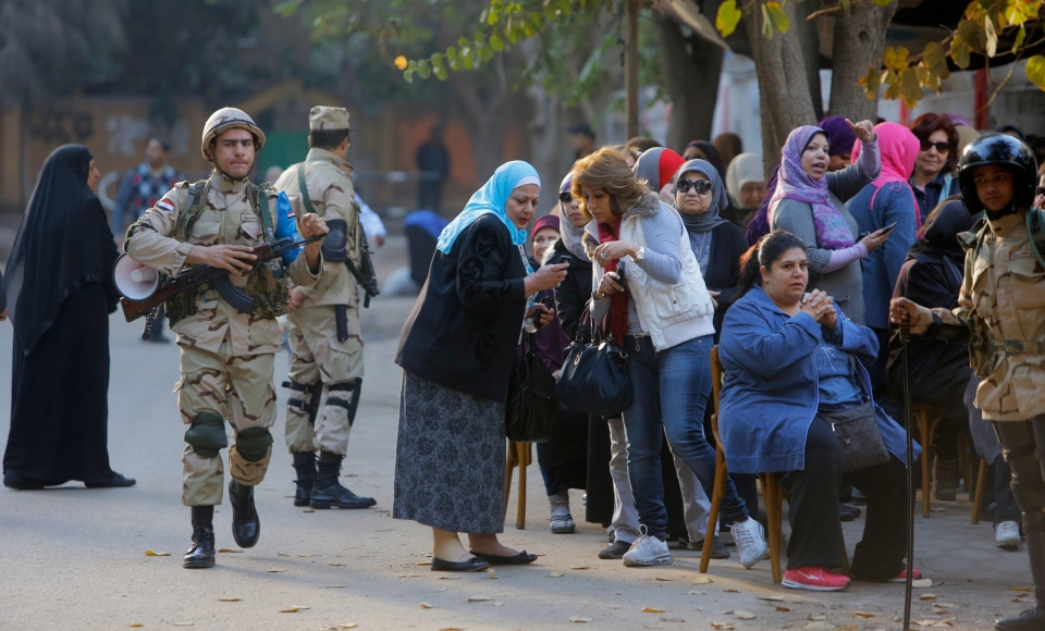 Egyptian army soldiers stand guard as voters line up outside a polling station in Cairo, Egypt, Tuesday, Jan. 14, 2014. (AP / Amr Nabil)