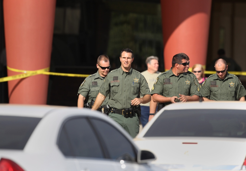 Pasco Sheriff Chris Nocco, front, walks out to update reporters after an argument between patrons over texting sparked a shooting that left one person dead and another injured in a Pasco County movie theater, Monday Jan. 13, 2014. (The Tampa Bay Times / Brendan Fitterer)
