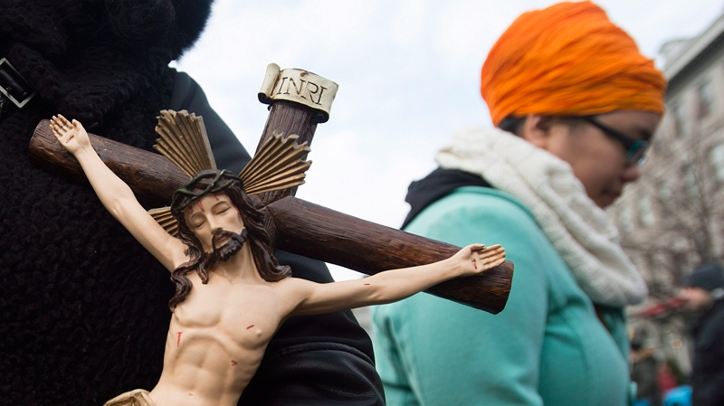 A woman holds a crucifix during a gathering to oppose the propsed Quebec Values Charter in Montreal, Sunday, Jan., 12, 2014. (Graham Hughes / THE CANADIAN PRESS)